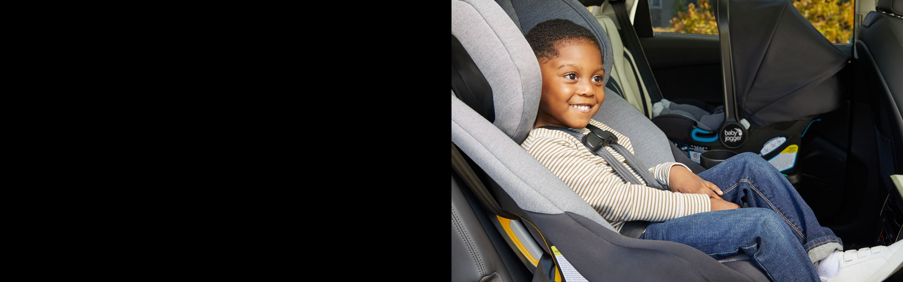 smiling child sitting in car seat in car