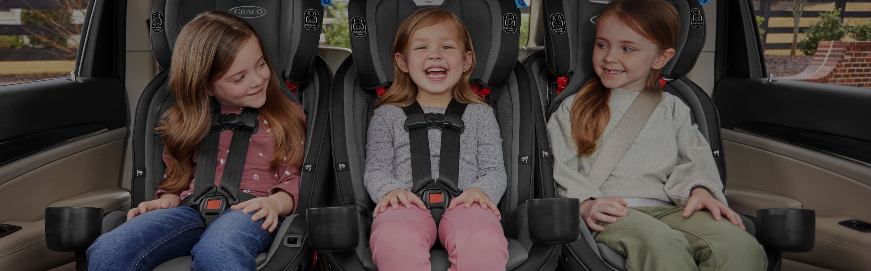 3 kids sitting in car seats in car