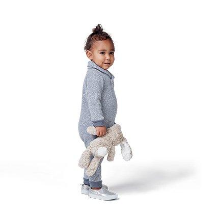 child smiling holding stuffed animal