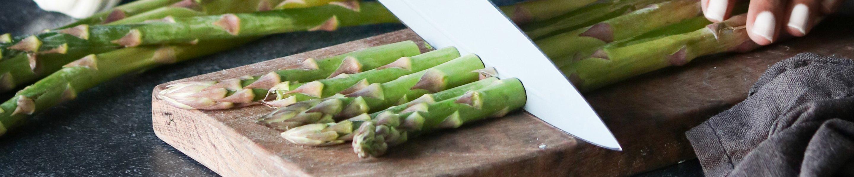 asparagus being cut on cutting block